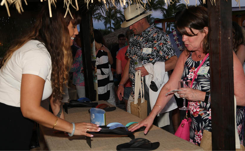 Incentive travel program attendees receiving flip flops on site