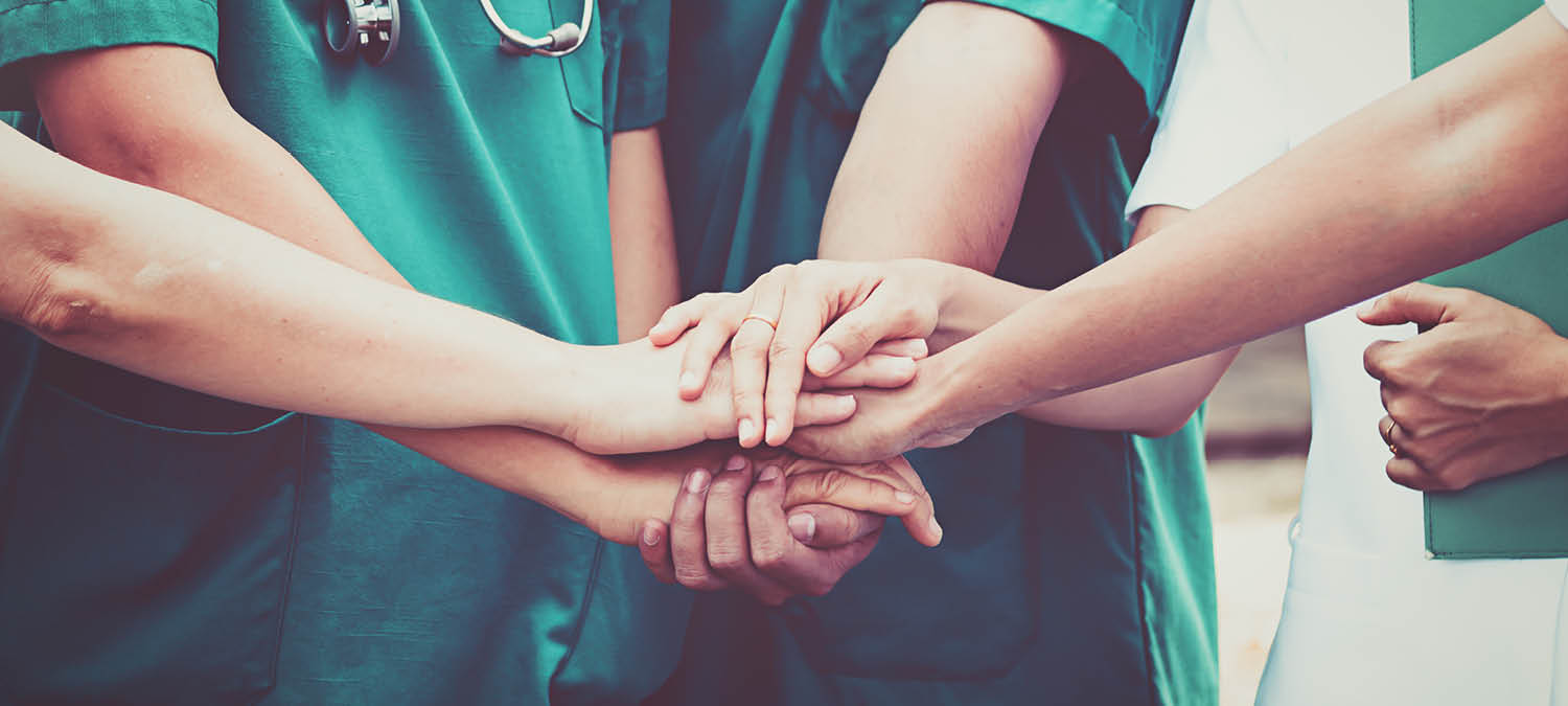 Group of healthcare nurses and doctors putting their hands in a huddle