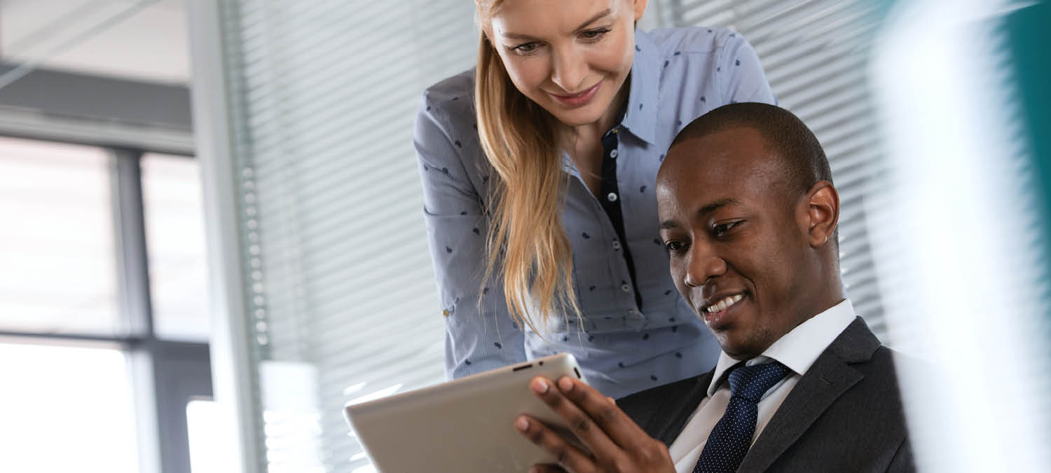 Man and woman in channel marketing looking at a tablet device together at work
