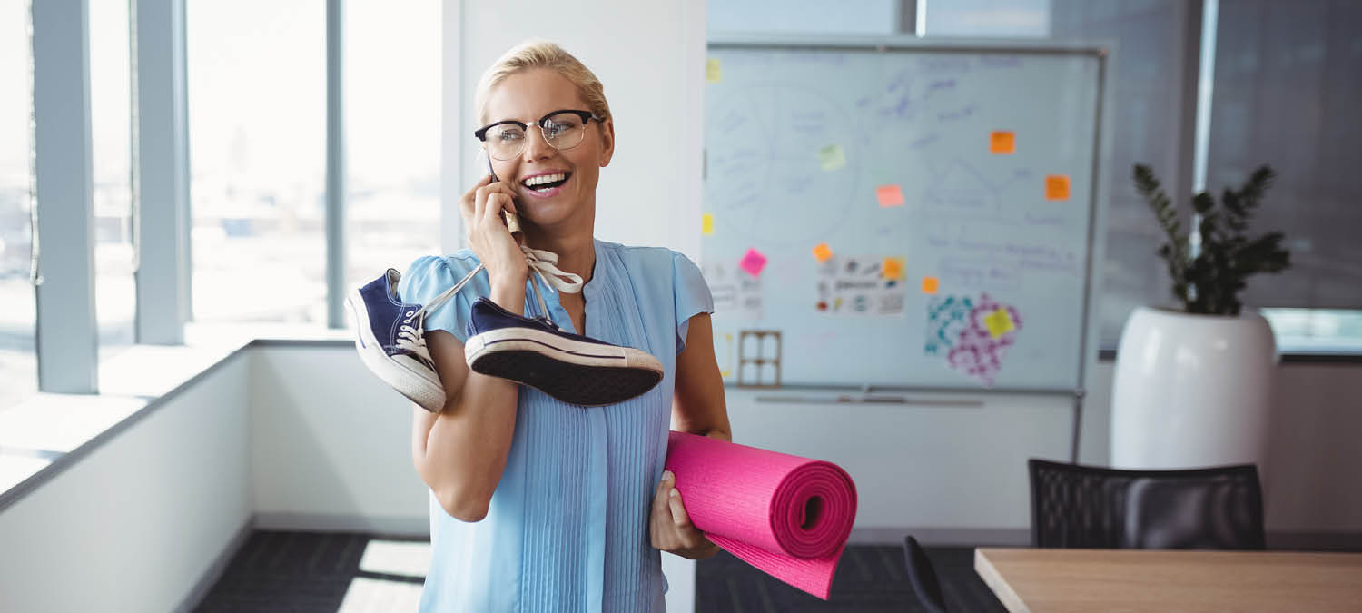 Woman talking on the phone carrying her shoes and yoga mat in an office