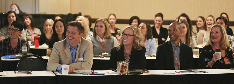 Group of engaged sales conference attendees listening to a keynote speaker