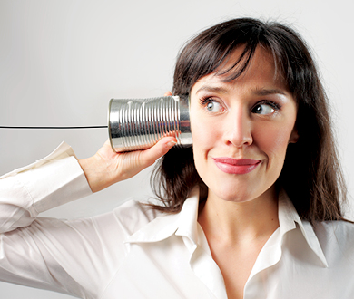 Woman holding a tin can telephone looking disengaged