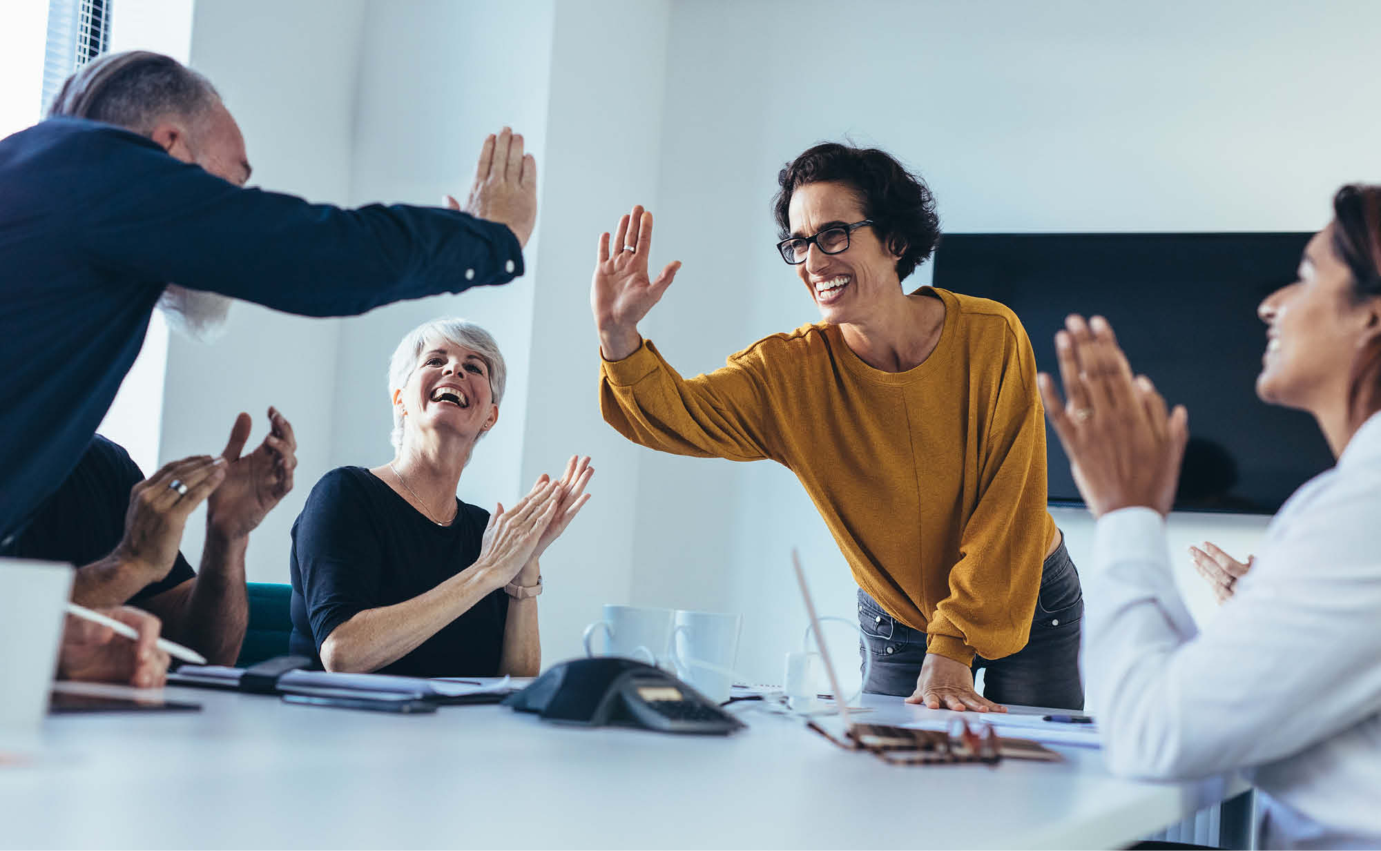 Group of happy, engaged employees giving each other high fives