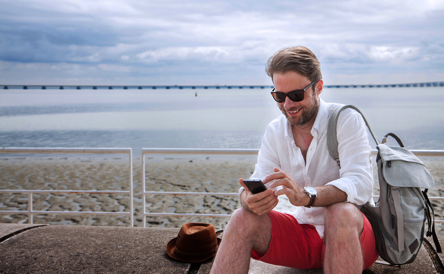 Man on an incentive travel trip smiling at his phone on the beach