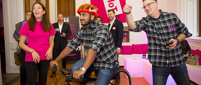 Event attendee riding a stationary bike while wearing a smart helmet as other attendees watch in the background