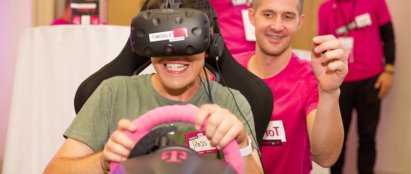 Event attendee driving a virtual reality car with T-Mobile event staff assisting in the background