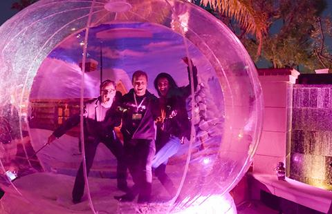 Three people in a bright pink human snow globe at an event