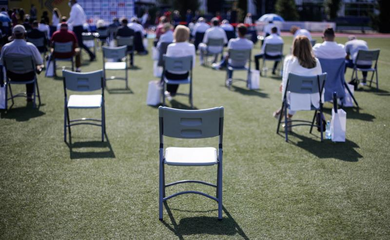 event attendees social distancing at outdoor meeting