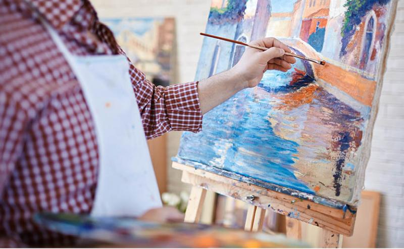 person painting on canvas