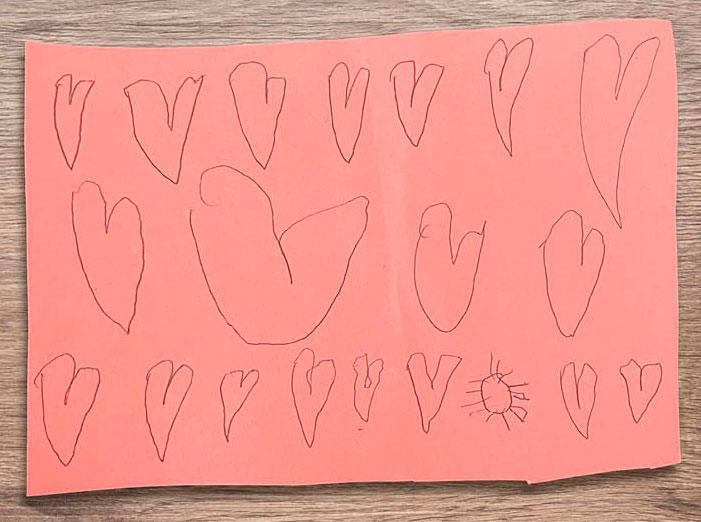 children's drawing of hearts on construction paper