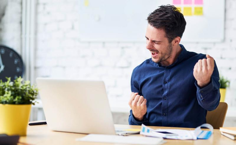 employee celebrating at desk while working remotely