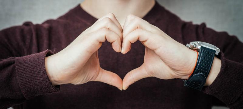 Person with their hands in a heart shape