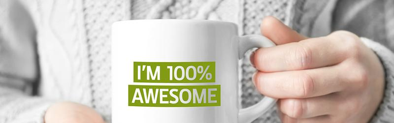 Employee holding up a coffee mug that says I'm 100% Awesome