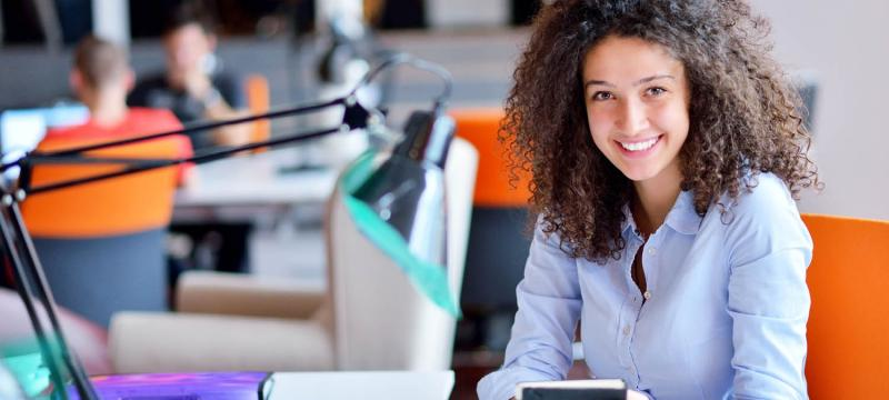 Happy woman employee smiling with a notebook at her desk