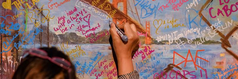 event attendee signing graffiti wall