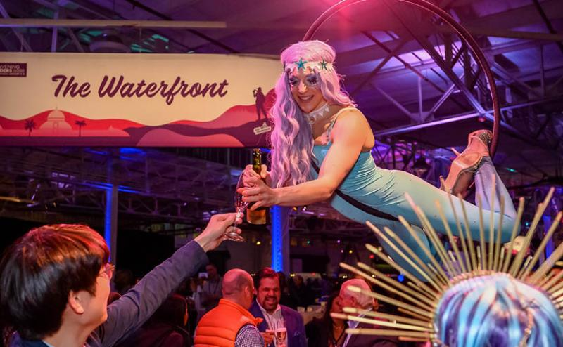 aerial acrobat serving drinks at an experiential event