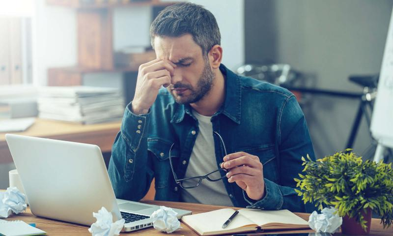 Stressed, disengaged new employee working at his desk