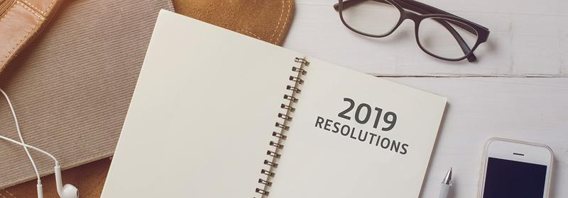 resolutions journal on desk with glasses and phone