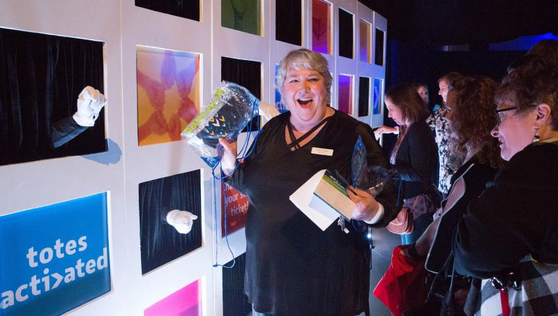 Event attendee recieving a swag bag from an interactive hand wall at an event