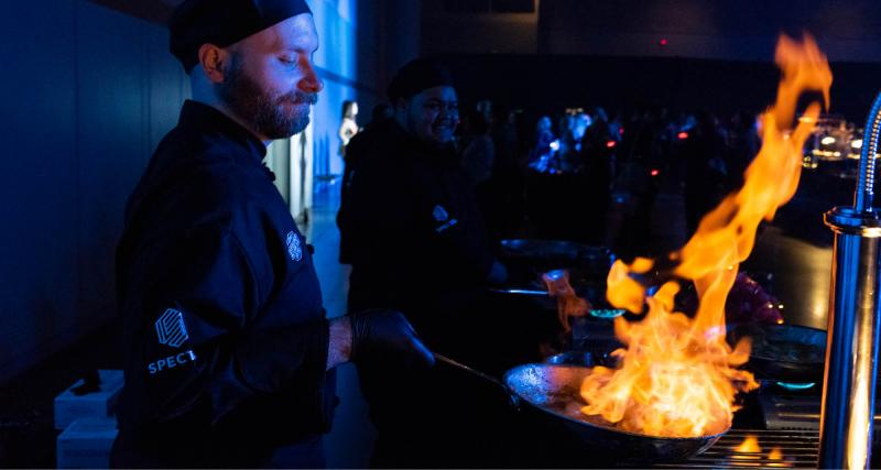 Chef at an event with flames in a skillet