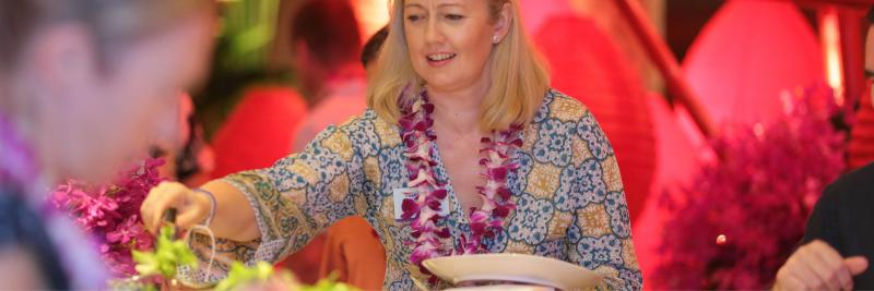 Event attendee grabbing food wearing a lei necklace