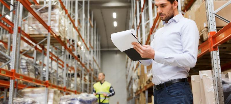 Man writing on a clipboard in a distribution center
