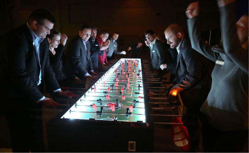 employees at event playing foosball