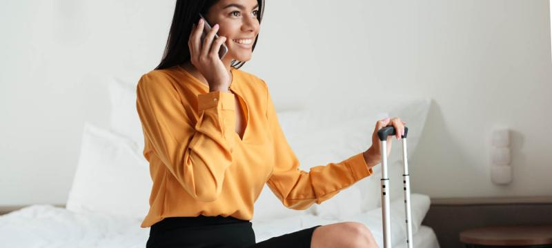 woman on the phone in a hotel room talking about her incentive travel trip