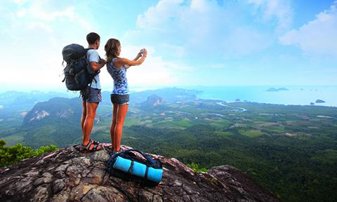 Couple taking a photo from a scenic overlook on an incentive trip