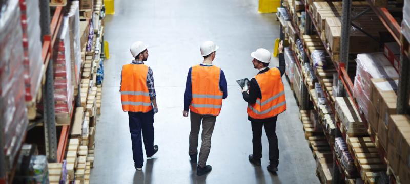 men with hard hats touring warehouse