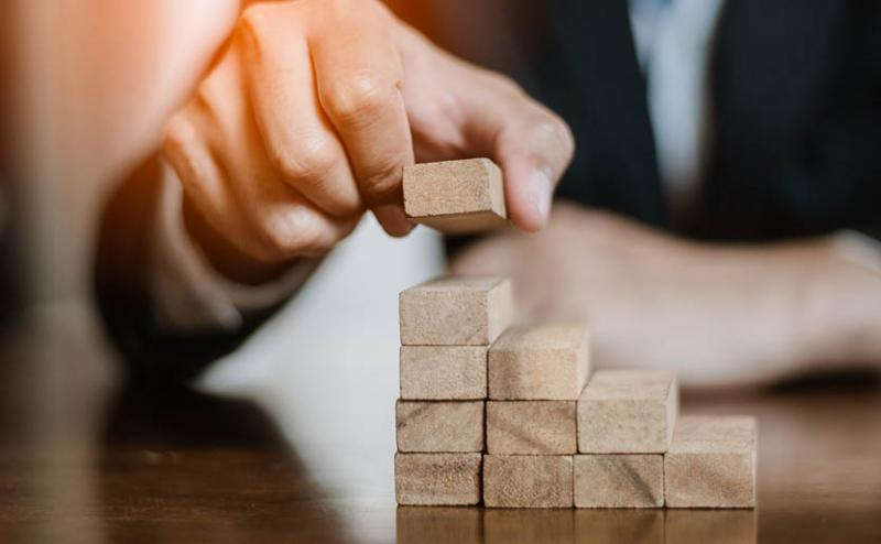 person stacking blocks representing channel partner recovery