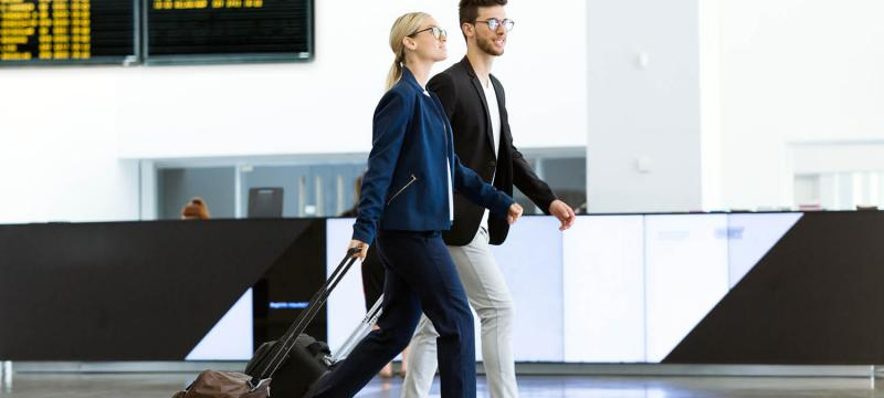 Man and women walking through an airport with rolling suitcases
