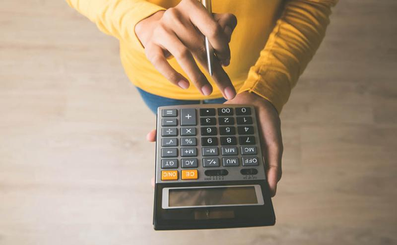 person using calculator to measure ROI for event