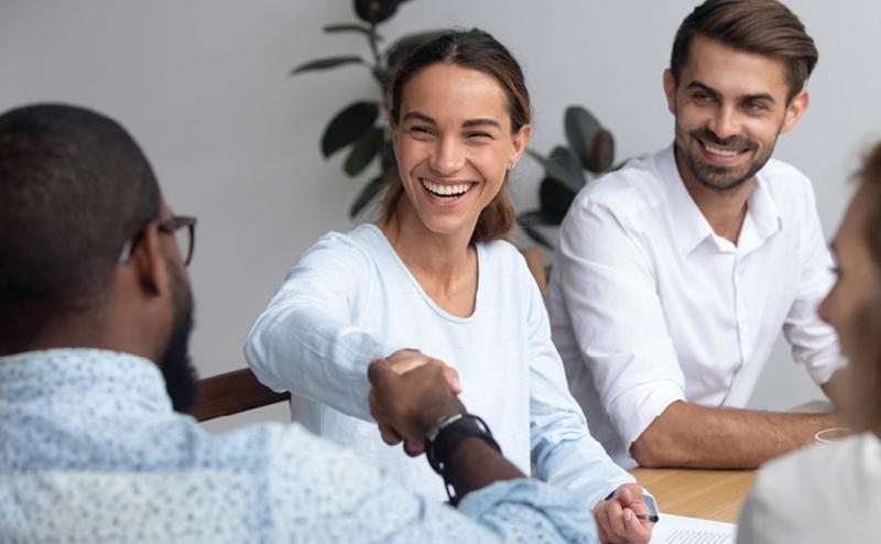 employees in bright office setting shaking hands