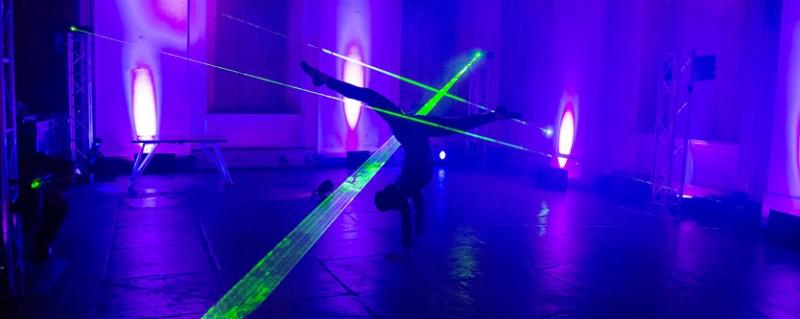 Acrobat navigating through a series of green laser beam lights in a room with purple uplighting