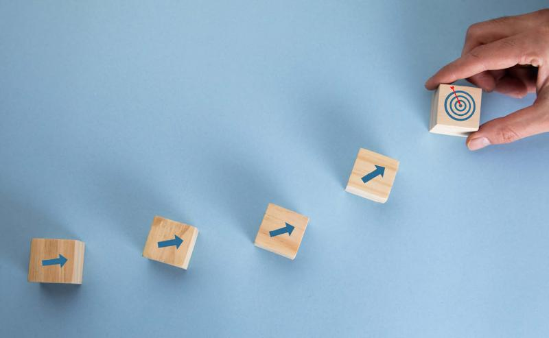 wooden blocks with arrows that point to target symbolizing process